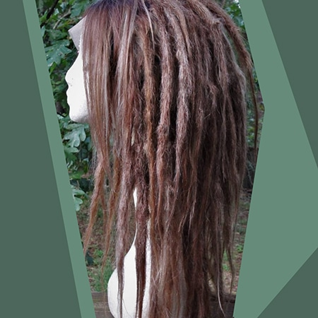 Straight burgundy brown dreadlocks on wig taken in a forest with plant and trees.